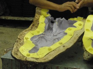 Wax casting: the flexible latex mold is held rigid in a plaster case and is now ready for wax casting.